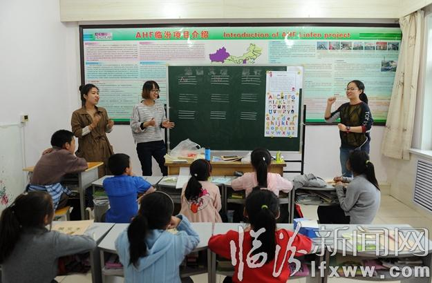 """山西师范大学外国语学院的青年志愿者在为孩子们上""""英情景语课""""."""
